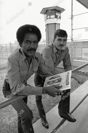 Wilbert Rideau, billy Sinclair Wilbert Rideau of Lake Charles, left, and Billy Sinclair of Baton Rouge, both serving life terms for murder, pose near a guard tower at the state prison at Angola, Louisiana, . The men, who are editors of the prison magazine, the Angolite, were named winners of a George Polk Award for special interest reporting