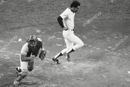 Ball flies over head of Los Angeles Dodgers catcher Steve Yeager as New York Yankees Mickey Rivers scores in third inning of World Series game with New York Yankees in New York. Yankees Thurman Munson singled to right, scoring Rivers and Roy White, and took second on the throw by Reggie Smith to the plate. When's Smith's throw sailed over Yeager's head, Munson went to third on the error. Yankees won, 12-2