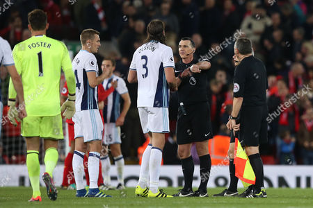 Referee Mr Neil Swarbrick points to his watch as Jonas Olsson argues with him at full time in the Premier League match between Liverpool and West Bromwich Albion played at Anfield, Liverpool on 22nd October 2016