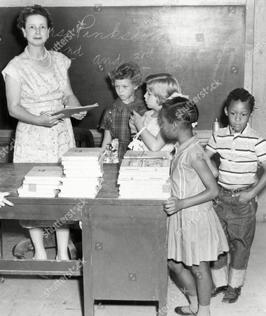 Stock Photo of Mrs. John Pinkston enrolls 2nd and 3rd graders at newly integrated classes in Springer, Okla., on . Getting ready to receive supplies are left to right Linda Smith, 8; Karita Ellis, 8; Eva Lois Wilson, 7; and Donald James Herndon, 7. Deputy Sheriffs were on hand for the start of enrollment, but there were no incidents. Two school board members were beaten at a recent board meeting in a dispute over integration of Springer schools this fall