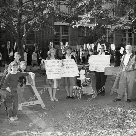Francis Arlen, left, Mrs. Susan Wicker with her daughter Marcy, 2½, and Mr. Larry Hochman, right, all from Bayside, New York, as they picketed the pickets at junior high school 109 in Queens Village, Queens on . A mask boycott of the city's schools started on September 14 to protest the city's integration methods