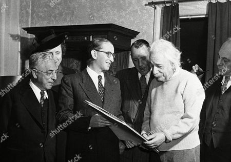 "Stock Image of Albert Einstein Dr. Albert Einstein accepts the score of ""Symphony David,"" a new musical composition dedicated to him by its composer Menachem Avidom, Secretary General of the Israel Philharmonic Orchestra, in a simple ceremony at his home in Princeton, N.J.,, on the occasion of the launching of the Orchestra's nationwide tour of the United States and Canada presented by the American Fund for Israel Institutions. Left to right: Oscar M. Lazrus, fund director; Mrs. Jean Norman, co-chairman Israel Advisory Board of American Fund, Mr. Avidom; Herbert Katzman, fund director, Prof. Einstein and Harry C. Oppenheimer, fund director"