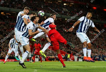 Jonas Olsson of West Bromwich Albion clears the ball under pressure from Joel Matip of Liverpool