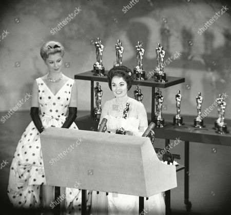 Actress Ann Blyth right holds the Oscar presented by the Motion Picture Academy for the best short subjects documentary, ?Glass,? produced by the Netherlands government. With her, at the Oscar presentations in Hollywood on is Mitzi Gaynor, who made the presentation