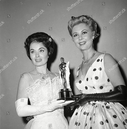 Ann Blyth holds Oscar presented by the Motion Picture Academy for the best short subjects documentary, ?Glass,? produced by the Netherlands government. With her is Mitzi Gaynor (polka dot dress), who made the presentation in Hollywood on