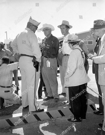 Three of the eleven members of a Non-Violent action against Nuclear Weapons project who were arrested at the Nevada test site in Las Vegas, are shown being stopped by an AEC guard. The group when told by guard they could not pass thru the gate were immediately arrested when they did so by Nye Co., Sheriff's Deputies. From left to right guard are: David Thompson, members; Lawrence Scott, Jim Peck and Lillian Willoughby