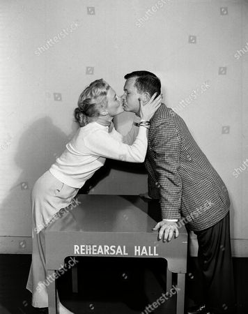 """Stock Image of Bob Thomas, Joan Caulfield Bob Thomas, AP Hollywood columnist, is all business as he rehearses a kiss with actress Joan Caulfield for her television show, """"My Favorite Husband"""" in Los Angeles on . He played the part of an extra who bought kisses from Miss Caulfield at a charity bazaar"""