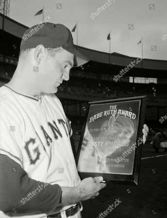 New York Giants' Dusty Rhodes' face is reflected in the Babe Ruth Award he received from the New York chapter of the Baseball Writers Association of America, at the Polo Grounds in New York, . Rhodes earned the honor for his hitting feats in last year's World Series against the Cleveland Indians