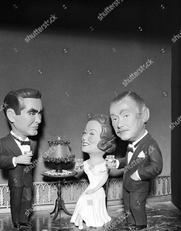 """Screen stars Tyrone Power, Gene Tierney and Herbert Marshall, left to right, are depicted in sculptures of balsa wood made by Bob Wallace, of Burbank, Calif., who does some expert whittling in his spare time,. The three are shown as they appear in the film """"The Razor's Edge."""" Wallace is an industrial illustrator for an aircraft company"""