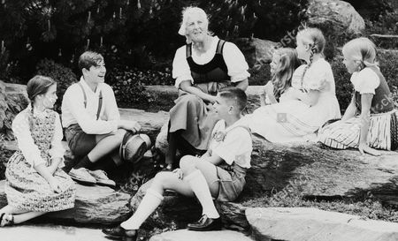 """Stock Picture of Baroness Maria Von Trapp with six children of the Stowe area who play the part of the family of Baron Von Trapp in """"The Sound of Music"""" based on life of the Baroness. Pictured in Garden of Trapp Lodge in Stowe, Vt., . From left to right are Jennifer Dumas, Bobby Anderson, Mrs. Trapp, Donald Gale, Melodee Page, Gene Whitley and Dia Elliman"""