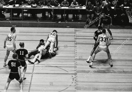 Don Reid of St. Louis is down along with Providence?s George Zalucki while Bill Nordmann of St. Louis almost spills on top of both in first half of National Invitation Tournament final at New York?s Madison Square Garden on . In foreground in providence?s Vince Ernst, who was named tourney?s most valuable player. Providence Friars won NIT Championship with 62-59 victory