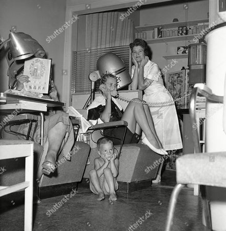 Hair stylist Pansy Phagan cools her heels as customer Dianne Hill uses the telephone in the midst of her date with the beauty parlor in Atlanta, in a posed setup to show some of the complaints on the part of the operators. The youngster is Terry McMillan, 3-year-old son of Mr. and Mrs. G.E. McMillan. He's just thrown in to illustrate one of the chief gripes against women who bring their children with them