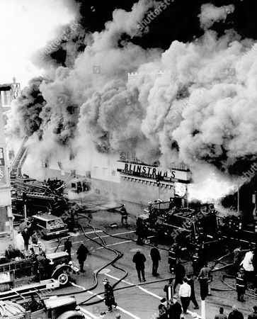 Stock Photo of Firemen battle blaze that destroyed Blinstrub's, one of the country's largest night clubs, in Boston, . Medieval style tower club barely shows in smoke at top. Bar area bursts with fire at right. Jimmy Durante was to have marked 75th birthday at party in club