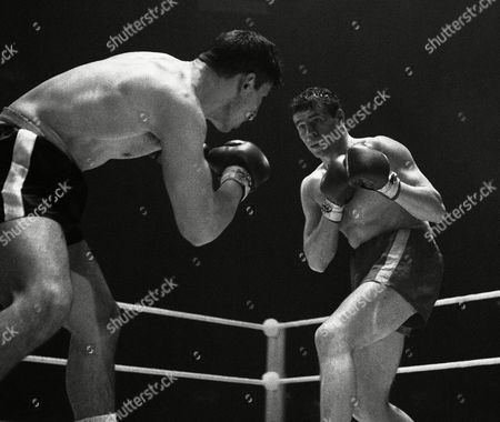 Terry Downes, right, London's ex-world champion, squares up to American Mike Pusateri during their 10-round international cruiserweight contest at Belle Vue, Manchester, Lancashire, on . Downes, former Middleweight champion, was awarded the verdict after five rounds. Pusateri, protégé of Rocky Marciano, suffered a badly bruised left eye and a cut on the cheekbone
