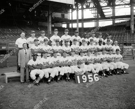 Stock Image of Charles DiGiovanna, Sandy Amoros, Joe Becker, Billy Herman, Jake Pitler, Walt Alston, Pee Wee Reese, Clem Labine, Carl Erskine, Dixie Howell, Gil Hodges. Carl Furillo, Lee Scott, Duke Snider, Sandy Koufax, Chico Fernandez, Charles Neal, Gino Cimoli, Ken Lehman, Randy Jackson, Jackie Robinson, Dale Mitchell, Harold Wendler, John Griffin, Al Walker, Ed Roebuck, Don Drysdale, Roger Craig, Don Newcombe, Jim Gilliam, Sal Maglie, Don Bessent, Roy Campanella The Brooklyn Dodgers of 1956 pose for a team photo at Ebbets Field, Brooklyn, New York, . Seated on ground in front is Charles DiGiovanna, clubhouse assistant. First row, from left: Sandy Amoros, Joe Becker, Billy Herman and Jake Pitler, coaches; Walt Alston, manager; Pee Wee Reese, Clem Labine, Carl Erskine, Dixie Howell, Gil Hodges and Carl Furillo. Second row, from left: Lee Scott, road secretary; Duke Snider, Sandy Koufax, Chico Fernandez, Charles Neal, Gino Cimoli, Ken Lehman, Randy Jackson, Jackie Robinson, Dale Mitchell and Harold Wendler, trainer. Third row, from left: John Griffin, clubhouse attendant; Al Walker, Ed Roebuck, Don Drysdale, Roger Craig, Don Newcombe, Jim Gilliam, Sal Maglie, Don Bessent and Roy Campanella