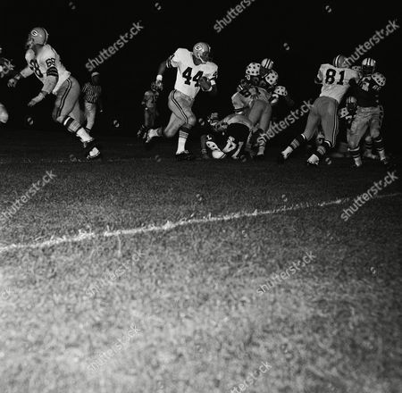 Stock Photo of Don Anderson (44), Green Bay Packers' halfback, skirts right end for good gain in third quarter of the College All-Star game, Chicago, Ill. Blocking for Anderson are Marv Fleming (81), and Ken Bowman (57). Identifiable All-Stars are Bill Staley (74), Utah State, Mike McGill (60), Notre Dame, and Fred Carr (86), Texas-El Paso. Packers won, 34-17