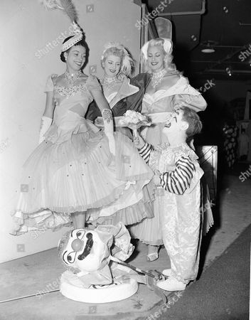 With a princely gesture, circus midget Prince Paul presents flowers to three English girls who are in the show, backstage during the New York run, . The girls are: left to right, Pat Cooper, who is from Devonshire; Shiley Coomas and Brinda Elliot, both of London
