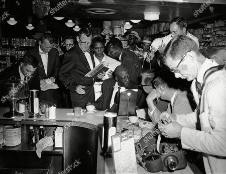 Stock Photo of Surrounded by newsmen and accompanied by an itinerant white minister, Rev T.D.R.V. Thompson, sits at the all-white lunch counter in Kress variety store in Dallas, Tex., after being the first black served in the initial attempt to integrate store lunch counters. Thompson, a Dallas minister, was accompanied by Ashton Jones, standing next to Thompson. Jones said he is a member of the Community Church of Los Angeles