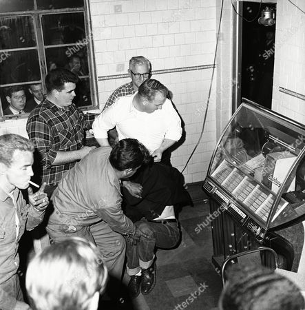 Stock Image of Charles Barnes Jr., white shirt, prepares to throw a sit-in demonstrator out of restaurant owned by his father, in checked shirt, immediately behind him, as other men help in Annapolis, Md., . Barnes refused service to this and 27 other demonstrators. Police arrested 16 of the integrationists when they wouldn?t move from the sidewalk