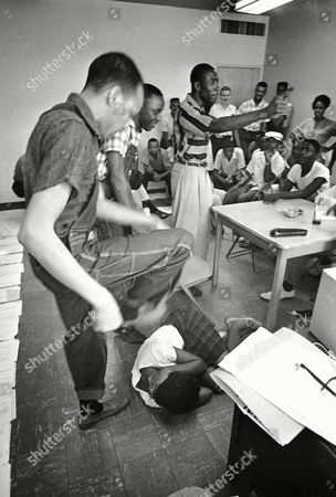 David Dennis, left, pretends to smash his foot into the body of Shirley Applewhite, on the floor, during school in Jackson, Miss., as African Americans learn how to defend themselves if attacked during sit-ins, . Robert Frazier (striped shirt) yells for a 'waitress' to divert attention