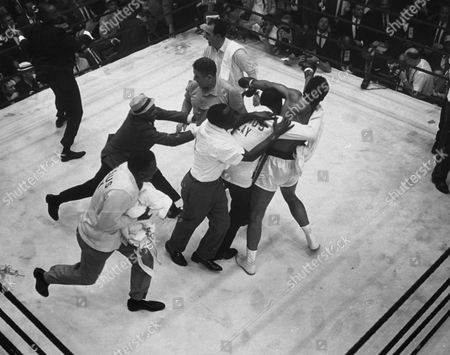 Stock Picture of Handlers of Cassius Clay swarm over him in the ring after referee Barney Felix, top center, awarded Clay a TKO victory at the start of the 7th round in the fight with Sonny Liston in Miami Beach, Florida, . Liston suffered a shoulder injury in addition to a deep gash under the left eye