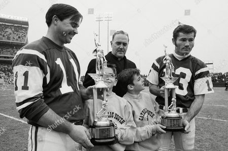 Jim Turner, left, of the New York jets is presented with trophy as the New York Catholic Youth Organization's most popular player, by Thomas Lambertson, 11, at New York's Shea Stadium, . At right is Don Maynard, last year's most popular Jet. Maynard receives his trophy from Kevin Rehill. At rear is Msgr. Philip J. Murphy, New York CYO director. Last year award was not presented due to the death of Cardinal Francis Spellman