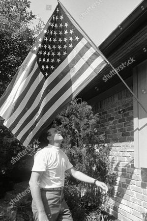 Stock Photo of Dean Armstrong Dean Armstrong, brother of Astronaut Neil Armstrong, puts the flag in place at the Neil Armstrong home near the Manned Spacecraft Center, Houston, Tex. Dean, from Anderson, Ind., is a house guest while his brother is making history by landing and walking on the moon with his fellow astronaut Edwin E. Aldrin
