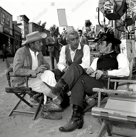 """Dmytryk Quinn Fonda Film actors Anthony Quinn, center, and Henry Fonda, right, talk with director Edward Dmytryk on the back lot of a Hollywood movie studio during a break in production of """"Warlock"""" on"""
