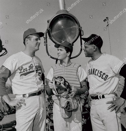 Two rivals during the baseball season, Don Drysdale, left, of the Los Angeles Dodgers, and Willie Mays, right, of the San Francisco Giants, chat about baseball with actor Paul Peterson, center, while waiting a camera call on the set of The Donna Reed Show. The two ball players are working together for the first time on TV