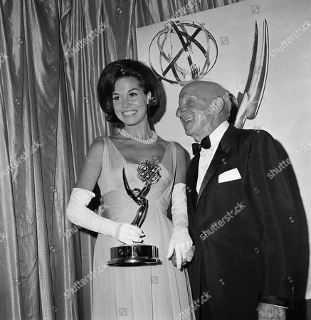 Mary Tyler Moore, who plays Dick Van Dyke's wife on his television show, holds the Television Academy Emmy for outstanding individual achievement awarded to him, in Hollywood, Calif., . With her is Jimmy Durante who made the presentation. Van Dyke, a previous Emmy winner, was not present at the awards show