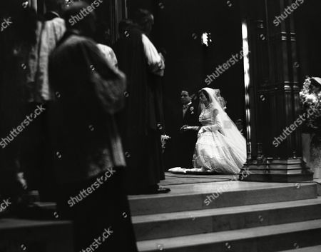 Robert Sargent Shriver, Jr., and his bride, Eunice Kennedy, principals in one of New York's biggest marriage affairs, john hands at the altar of St. Patrick's Cathedral during the solemn wedding ceremony in New York, . The bride is the daughter of Joseph P. Kennedy, wealthy industrialist and former diplomat. More than 2,500 guests, including numerous notables, attended the ceremony