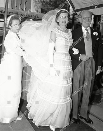 Eunice Mary Kennedy, about to wed in one of New York's most sumptuous social events, arrives at St. Patrick's Cathedral in New York on the arm of her father, Joseph P. Kennedy, former U.S. ambassador to the court of St. James, . A bridesmaid lends a hand as the wind billows the bridal gown. Miss Kennedy became the bride of Robert Sargent Shriver, Jr., of Chicago