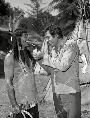 "Fess Parker, star of the NBC-TV ""Daniel Boone"" show, lights the cigar of singer-actor Ed Ames, . Parker was passing out cigars between takes on the set, celebrating the birth of a daughter, Ashley Allen, in a Santa Monica hospital on October 19. The Parkers have a three-year-old son, Fess III"
