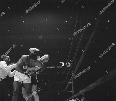Stock Photo of Floyd Patterson, George Chuvalo, Zach Clayton Referee Zach Clayton moves in to break George Chuvalo away from a clinch with Floyd Patterson. He grips Chuvalo's right arm, but Chuvalo breaks free and swings at Patterson's head. Clayton again grabs his arm breaking up the action. Sequence came in second round of 12-round fight in New York's Madison Square Garden
