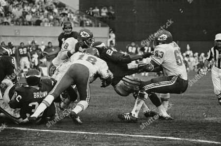 Minnesota Vikings' ball carrier Clinton Jones (26) is caught between Kansas City Chiefs Willie Lanier (63), Emmitt Thomas (18) and Bobby Bell (78) in first half of National Football Conference game on in the Twin Cities, Minneapolis. Jones gained 3 yards on the play