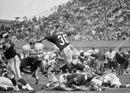 Minnesota Vikings ball carrier Bill Brown leaps over linemates for 2-yard gain against the Kansas City Chiefs in Minneapolis, on during National Football Conference game in Twin Cities Chief's Willie Lanier (63) waits for Brown while Vikings Milt Sunde (64) falls on Chiefs player