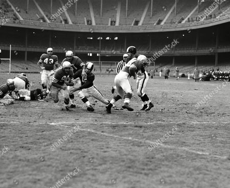 John Strzykalski (91), San Francisco Forty-Niners' halfback, eludes tackle try of New York's end Bruce Alford (12) to score touchdown in ginning period of pro gird contest at Yankee Stadium in New York on . The runner scored from Yanks' Seven-yard line. Giving him a little help against Yank tackler is his teammate, end Gordy Soltau (51). Other identifiable player is 49ers' tackle Ray Collins (43, left