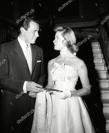 """John Forsythe, actor, talks to Natalie Trundy, young New York actress, at the opening of """"The Ambassador's Daughter"""" at the Paramount Theater in New York"""