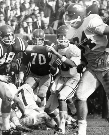 A startled Arkansas quarterback Bill Montgomery (10) watches a pitchout go astray as he is pressured by Ole Miss defenders Dennis Coleman (48) and Buz Morrow (70) in Sugar Bowl action in New Orleans, . Fullback Bruce Maxwell, foreground, continues unconcernedly