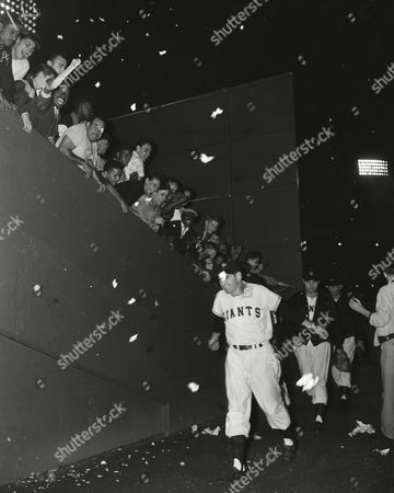 Dusty Rhodes of the New York Giants walks through a confetti shower from the bleachers as he enters the Polo Grounds clubhouse, after his pinch single in the 13th inning scored two runs to defeat the Brooklyn Dodgers 4-3 in the first game of the three-game series