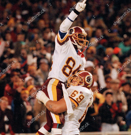 Redskins wide receiver Gary Clark (84) celebrates with guard Mark Schlereth (69) after Clark caught a 50-yard touchdown pass from Mark Ryplen in the fourth quarter of a game against the New York Giants at RFK Stadium in Washington on . The Redskins won 34-17