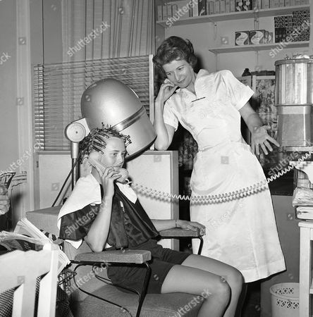 Hair stylist Pansy Phagan cools her heels as customer Dianne Hill uses the telephone in the midst of her date with the beauty parlor in Atlanta on in a posed setup to show some of the complaints on the part of the operators. The youngster is Terry McMillan, 3-year-old son of Mr. and Mrs. G.E. McMillan. He's just thrown in to illustrate one of the chief gripes against women who bring their children with them