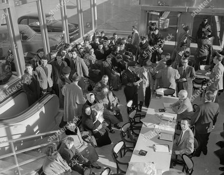 Women in babushkas hold infants while awaiting their turn to get immigration clearance after a plane-load of Hungarian refugees set down at Gen. Billy Mitchell airport in Milwaukee. Zoltan Varga, who walked 250 miles to the Austrian border, stands fourth from left, front row, in the group near the windows