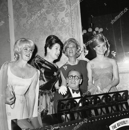 """Irving Berlin is joined by Ginger Rogers, Rosalind Russell, Dinah Shore and Yvette Mimieux, left to right, as the 75-year-old composer plays his well known """"Always,"""" in Hollywood, . The occasion was the big night for Berlin, staged by the Screen Producers Guild"""