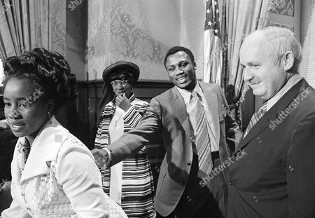 Joe Frazier, John C. West Heavyweight boxing champ Joe Frazier reaches for his wife who stepped out of line to retrieve a jewelry box, a present from Gov. John C. West, right in Columbia, South Carolina on . Seemingly wondering what's going on is Frazier's mother with hand to chin. Frazier afterwards addressed the South Carolina General Assembly