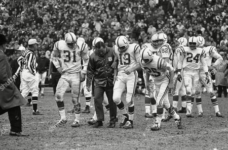 Johnny Unitas Coach Don Shula and anxious teammates crowd around injured quarterback John Unitas as he limps from the field during the second quarter of game against the Chicago Bear on in Baltimore. At right is Alex Hawkins. Unitas later underwent surgery on torn right knee ligaments. Unitas will miss the last two regular season games and probably the National Football League title game on January 2, should the Colts qualify by winning the Western Conference championship