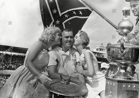 Junior Johnson Junior Johnson of Ronda, N.C., winner of the 13th Annual Southern 500 at the Darlington (S.C.) International Raceway, receives kisses from Miss Ginger Pointevint, Miss Sun Fun U.S.A., left, and Miss Joyce Brown, Miss Southern 500