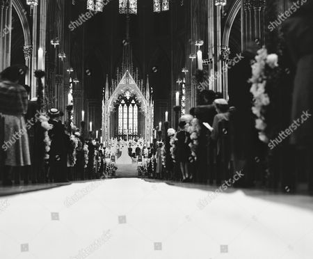 Guests fill the flower-decorated pews of St. Patrick's Cathedral in New York, to watch the wedding of Robert Sargent Shriver Jr., and Eunice Kennedy, who kneel at the altar as Cardinal Francis Spellman performs the solemn ceremony. The bride is the daughter of wealthy wartime ambassador to Britain Joseph P. Kennedy. A guest list of 2,500 notables helped make the wedding one of New York's most sumptuous events in years