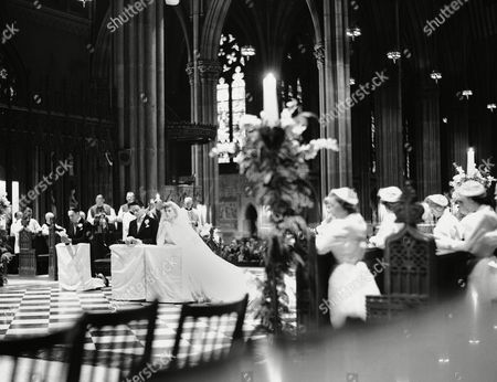 Robert Sargent Shriver, Jr., and his bride, the former Eunice Mary Kennedy, kneel at the altar of St. Patrick's Cathedral in New York, during their solemn nuptial services. The bride, daughter of ex-diplomat Joseph Kennedy of Hyannis Port, Mass., and Palm Beach, and her bridegroom were wed before 2,500 notables in ceremonies performed by New York's Cardinal Francis Spellman