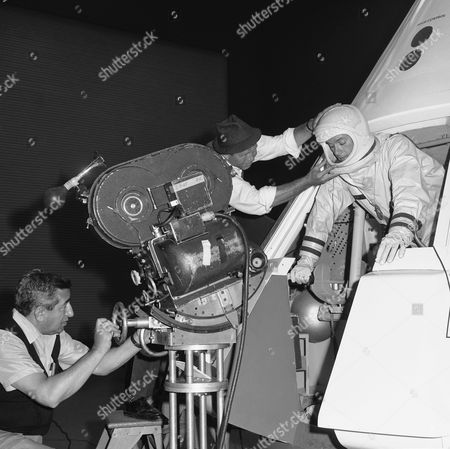"""Television show; TV Show From left, cameraman Sam Rosen and director Gero Nelson guide the co-star of the series """"I Dream of Jeannie,"""" Larry Hagman, as he emerges from a mockup of the Apollo space vehicle, filming at North American Aviation's Space Division in Downey, Calif"""